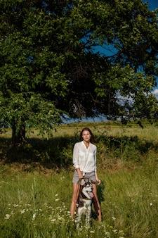 Belle jeune femme à la mode en short en jean et un chemisier blanc posant dans le parc avec un husky