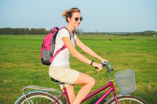 Belle jeune femme monte sur un vélo en été sur le fond des champs verts