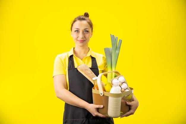 Belle jeune femme montrant la boîte de légumes, fruits, produits éco frais