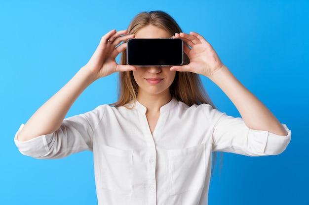 Belle jeune femme montrant l'écran du smartphone sur fond bleu