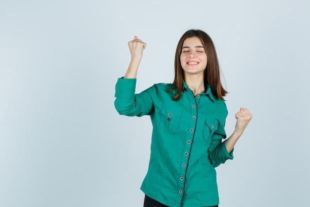 Belle jeune femme montrant le geste du gagnant en chemise verte et regardant heureux, vue de face.