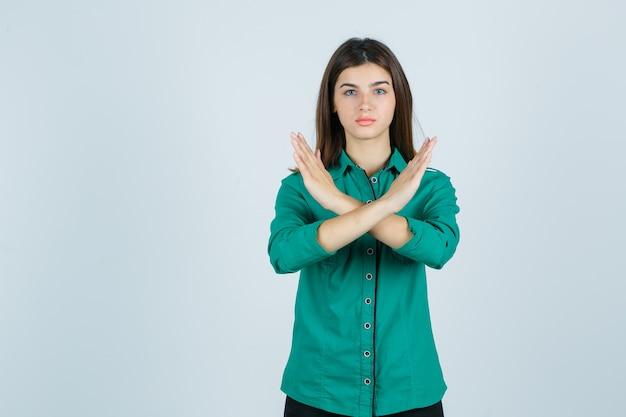Belle jeune femme montrant un geste de refus en chemise verte et à la vue sérieuse, de face.
