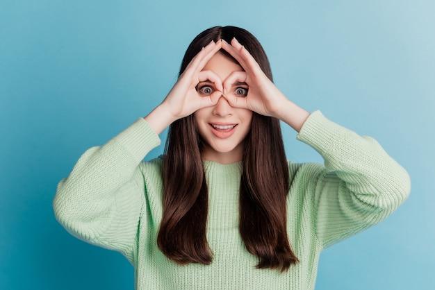 Belle jeune femme montrant le signe ok couvrir les yeux des jumelles geste sur le mur turquoise