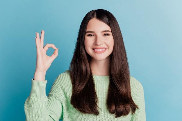 Belle jeune femme montrant le signe ok sourire brillant à pleines dents sur le mur sarcelle