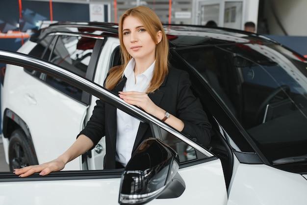 Belle jeune femme montrant son amour pour une voiture dans une salle d'exposition de voiture