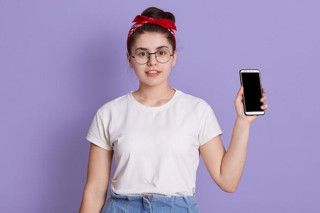 Belle jeune femme montre à droite dans l'écran blanc de l'appareil photo du téléphone intelligent isolé sur l'espace lilas