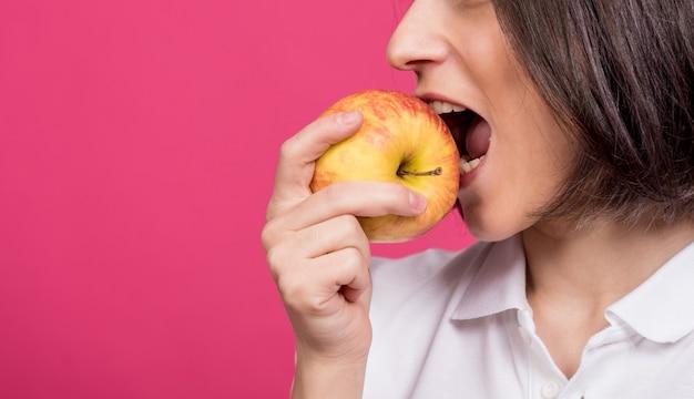 La belle jeune femme mord une grosse pomme