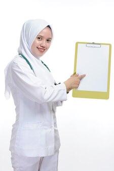 Belle jeune femme musulmane infirmière ou médecin pointant le papier vierge au presse-papiers isolé sur fond blanc
