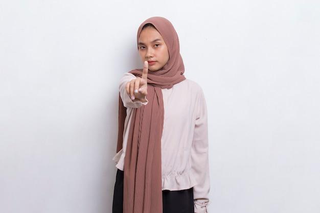 Belle jeune femme musulmane avec la main ouverte faisant un panneau d'arrêt avec un geste de défense d'expression sérieuse