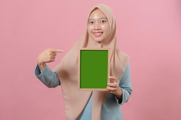Belle jeune femme musulmane pointant et montrant quelque chose sur un tableau sur fond rose