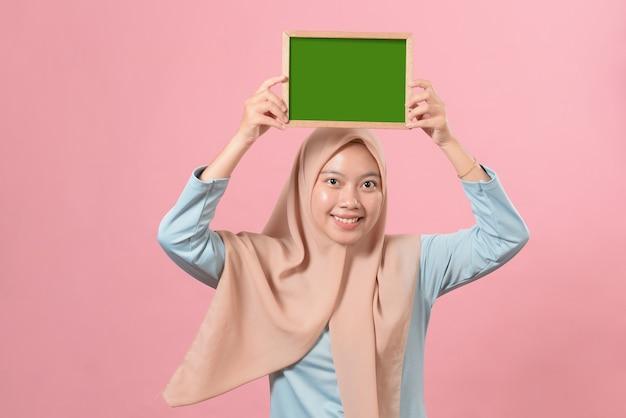 Belle jeune femme musulmane tenant et montrant quelque chose sur un tableau sur fond rose