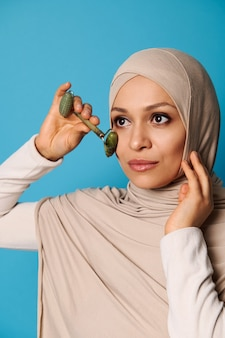 Une belle jeune femme musulmane avec la tête couverte en hijab faisant un massage du visage avec un rouleau de jade.