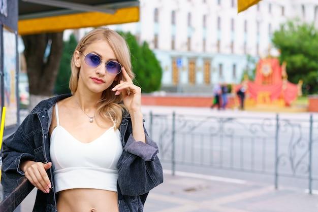 Belle jeune femme de nationalité kakaz pose l'après-midi dans la rue de la ville dans un survêtement blanc et un jean bleu femme blonde confiante dans des lunettes de soleil en été