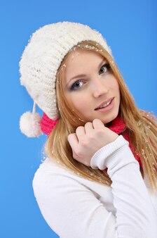 Belle jeune femme avec de la neige sur bleu