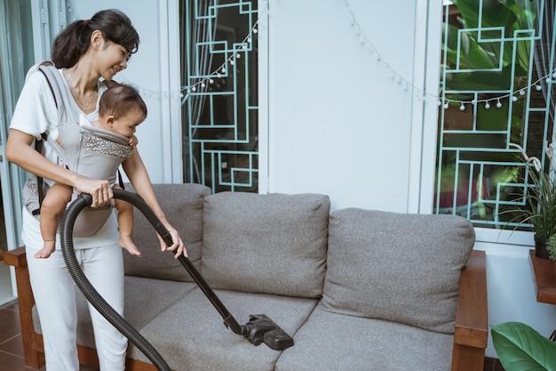 Belle jeune femme nettoyage avec aspirateur à la maison