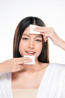 Belle jeune femme nettoyant le visage en coton