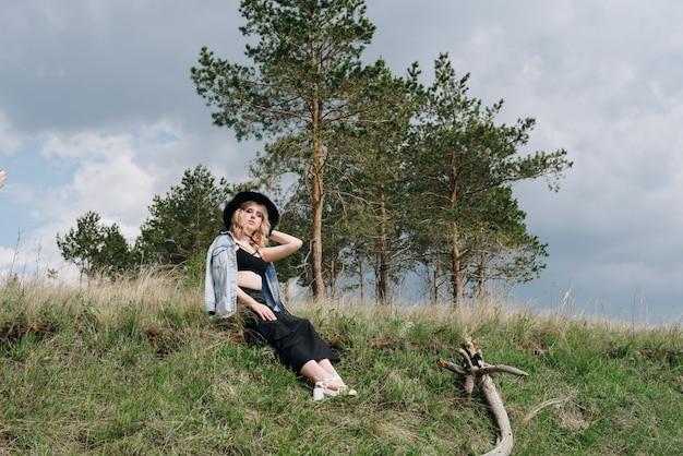 Belle jeune femme en noir contre un paysage de ciel et champ 1