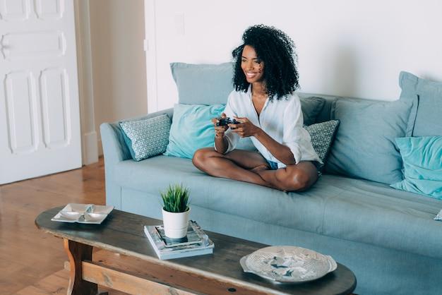 Belle jeune femme noire assise dans le canapé, jouer à des jeux vidéo