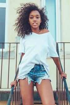 Belle jeune femme noire dans les escaliers posant