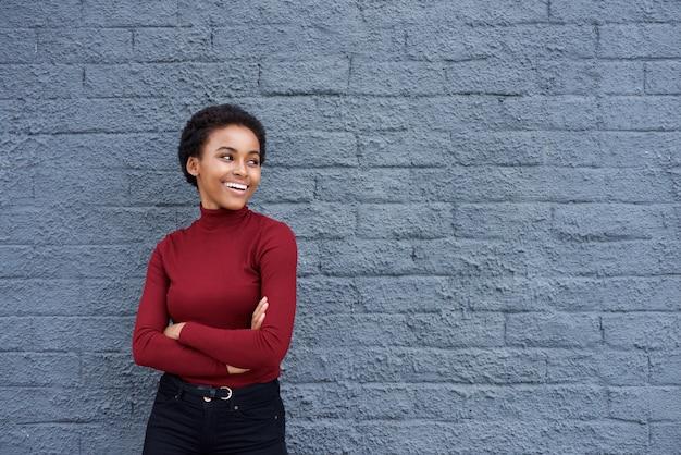 Belle jeune femme noire souriant contre le mur gris