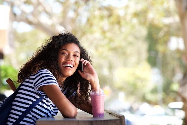 Belle jeune femme noire souriant et parlant au téléphone portable