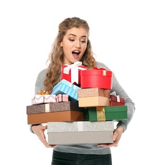 Belle jeune femme avec de nombreux coffrets cadeaux sur blanc