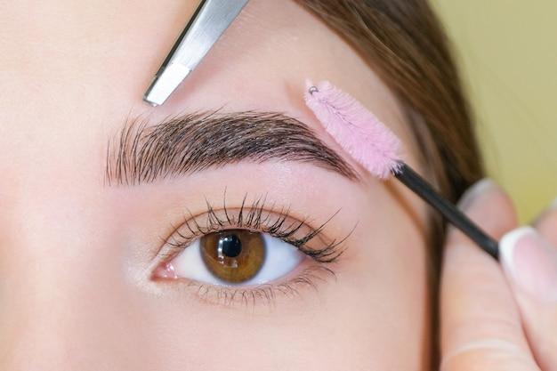 Belle jeune femme a obtenu la correction des sourcils dans un salon de beauté