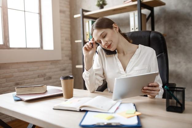 Belle jeune femme occupée s'asseoir à table dans la chambre. elle parle au téléphone et regarde le cahier. modèle tenir le stylo et la tablette.