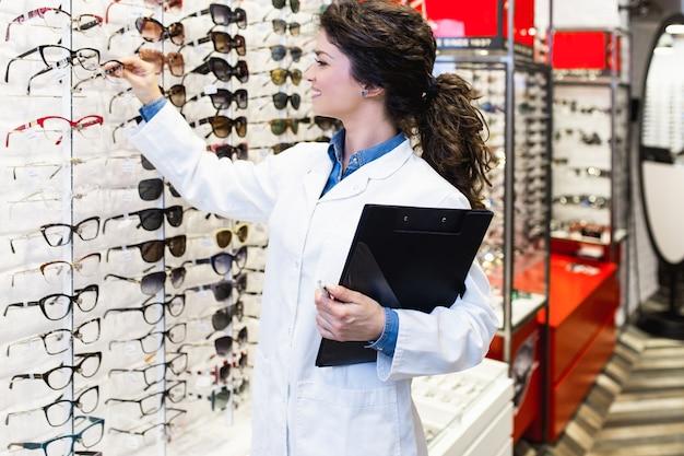 Belle jeune femme ophtalmologiste debout dans un magasin d'optique.