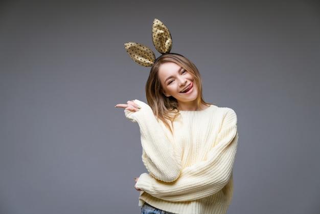 Belle jeune femme en oreilles de lapin doré montre la langue et le doigt sur le côté sur le mur gris
