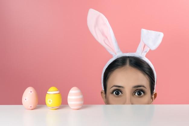 Belle jeune femme avec des oreilles de lapin rose et des oeufs de pâques sur rose.