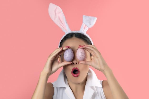 Belle jeune femme avec des oreilles de lapin rose tenant un oeufs de pâques colorés devant ses yeux.