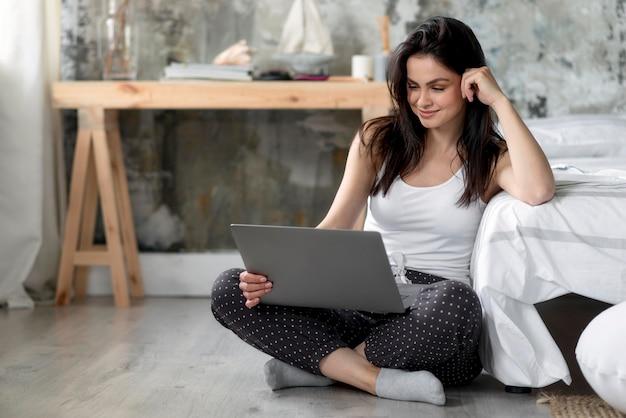 Belle jeune femme parcourant un ordinateur portable