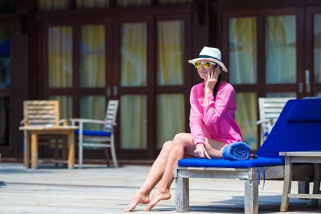 Belle jeune femme parlant par téléphone sur la plage blanche