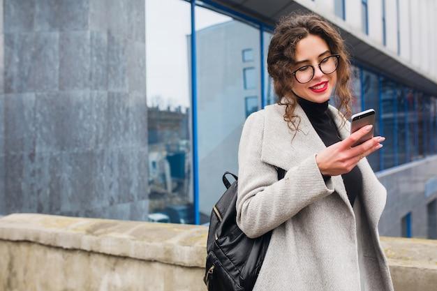 Belle jeune femme parlant sur smartphone, style de ville de rue automne, manteau chaud, lunettes, heureux, souriant, tenant le téléphone à la main, cheveux bouclés