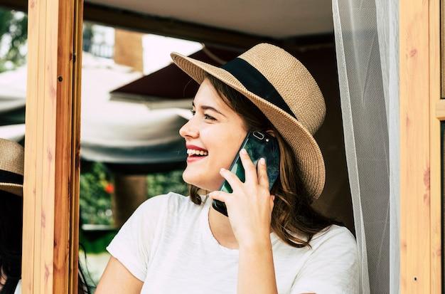 Belle jeune femme parle au téléphone en appelant des amis en plein air