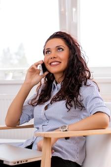 Belle jeune femme parle au téléphone portable à la maison