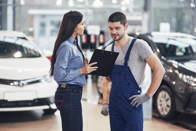 Belle jeune femme parle à un beau mécanicien automobile tout en réparant une voiture chez le concessionnaire