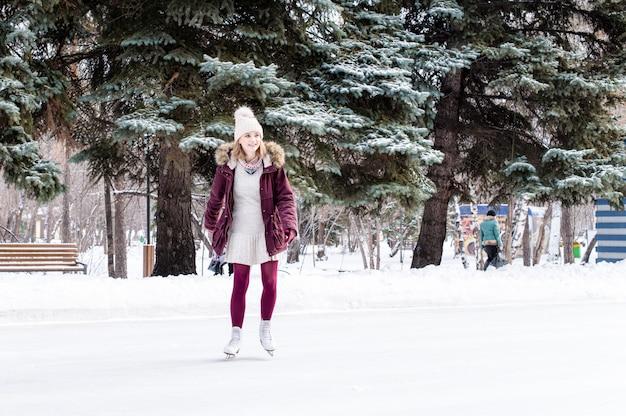 Belle jeune femme patinant dans le parc d'hiver enneigé