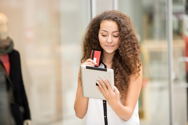 Belle jeune femme payant par carte de crédit pour faire du shopping