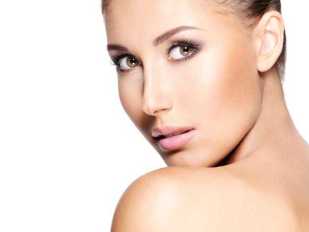 Belle jeune femme à la peau claire qui regarde la caméra; gros plan, isolé sur blanc.