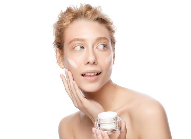 Belle jeune femme à la peau claire tenant un pot cosmétique et appliquant une crème pour le visage