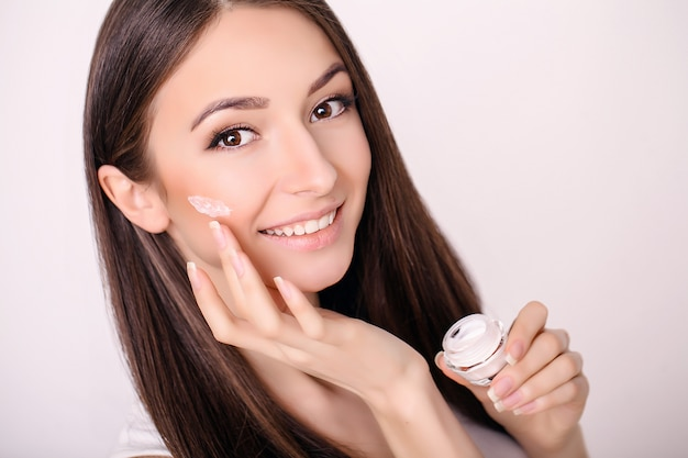 Belle jeune femme à la peau douce et propre touche son visage. traitement facial . cosmétologie, beauté et spa.