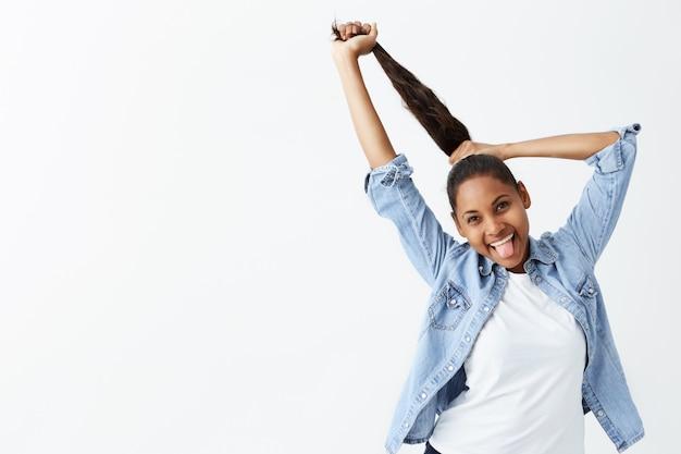 Belle jeune femme à la peau foncée habillée avec désinvolture et souriant en jouant avec sa queue de cheval. fille afro-américaine brune posant isolé sur mur blanc.