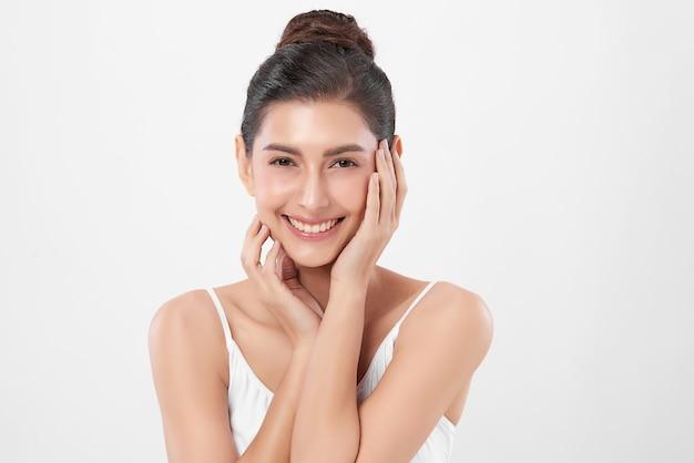 Belle jeune femme avec une peau fraîche et propre sur un mur blanc