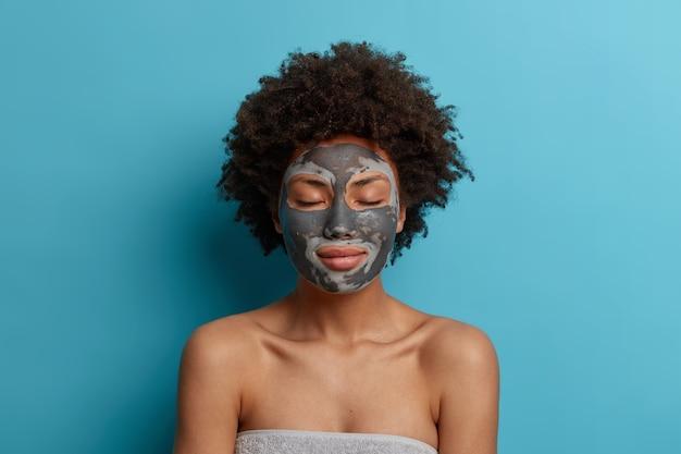 Belle jeune femme a une peau fraîche et propre, porte un masque d'argile de beauté sur le visage, se tient les yeux fermés, se soucie du corps après la douche, bénéficie de soins de beauté, se tient avec les épaules nues