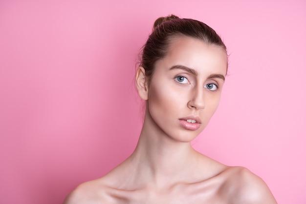 Belle jeune femme avec une peau fraîche et propre sur rose