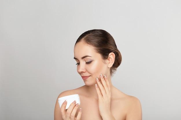 Belle jeune femme à la peau fraîche et propre touche son propre visage. fille tenant et appliquer une crème hydratante.