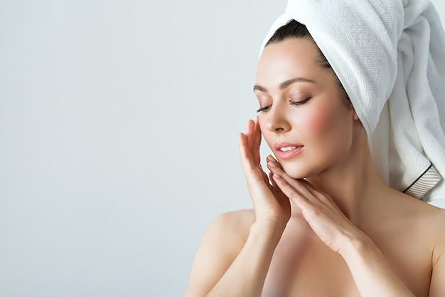 Belle jeune femme avec une peau parfaite, touchant son visage. concept de cosmétologie, de beauté et de spa.