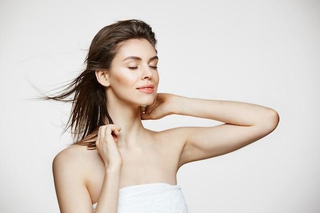 Belle jeune femme avec une peau parfaitement propre, souriant, toucher les cheveux sur le mur blanc. traitement facial. yeux fermés.